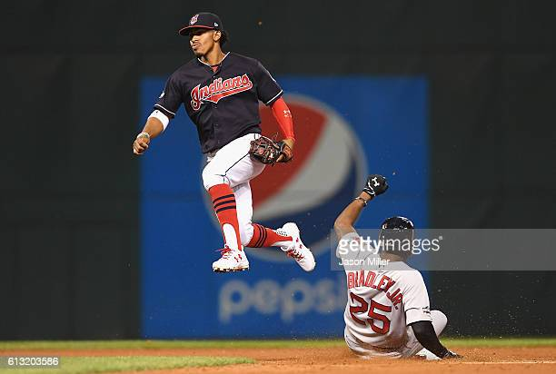 Francisco Lindor of the Cleveland Indians jumps into the air after forcing out Jackie Bradley Jr #25 of the Boston Red Sox at second base in the...