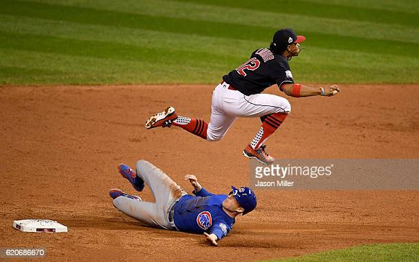 Francisco Lindor of the Cleveland Indians jumps over Chris Coghlan of the Chicago Cubs as Coghlan is out at second base in the ninth inning in Game...