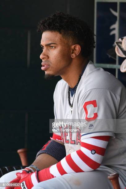 Francisco Lindor of the Cleveland Indians looks on from the dugout while wearing a red white and blue jersey and red and white stripe arm sleeve in...