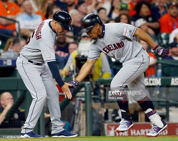 Francisco Lindor of the Cleveland Indians receives congratulations from third base coach Mike Sarbaugh after hitting a home run in the third inning...