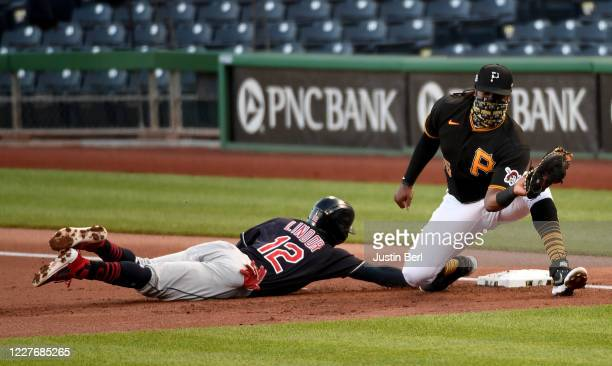 Francisco Lindor of the Cleveland Indians slides safely back into first base following a pickoff attempt by Josh Bell of the Pittsburgh Pirates in...