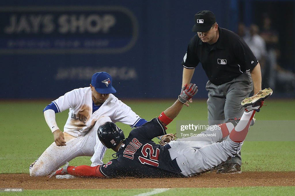 Francisco Lindor #12 of the Cleveland Indians slides safely into second base with a double in the eighth inning during MLB game action as he evades the tag by Ryan Goins #17 of the Toronto Blue Jays on September 1, 2015 at Rogers Centre in Toronto, Ontario, Canada.