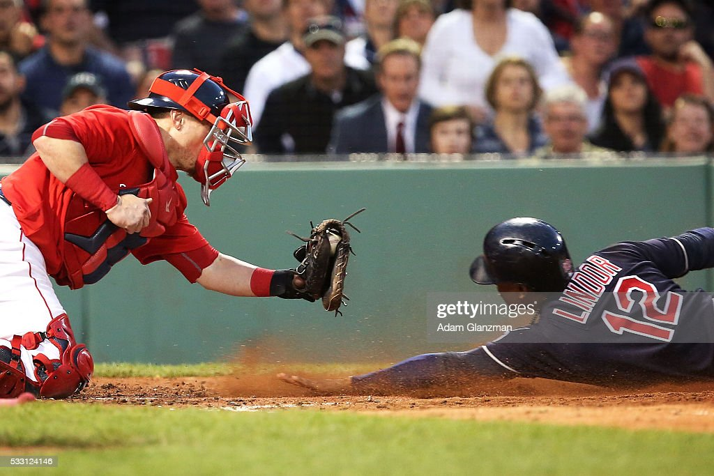 Francisco Lindor #12 of the Cleveland Indians slides under the tag of Christian Vazquez #7 of the Boston Red Sox in the third inning during the game at Fenway Park on May 20, 2016 in Boston, Massachusetts.