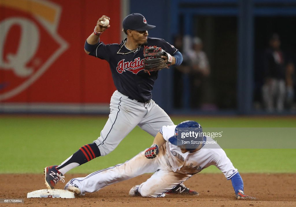 Francisco Lindor #12 of the Cleveland Indians turns a double play in the eighth inning during MLB game action as Darwin Barney #18 of the Toronto Blue Jays slides into second base at Rogers Centre on May 10, 2017 in Toronto, Canada.