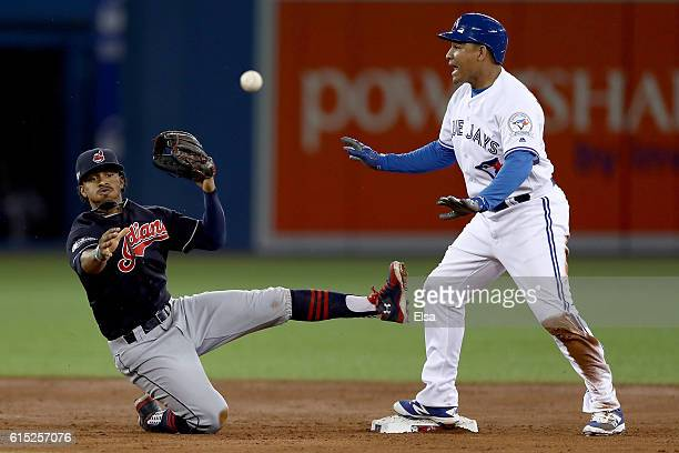 Francisco Lindor of the Cleveland Indians turns a double play tagging out Ezequiel Carrera of the Toronto Blue Jays at second base to end the second...