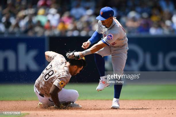 Francisco Lindor of the New York Mets tags Tommy Pham of the San Diego Padres on the head as he steals second base during the third inning of a...