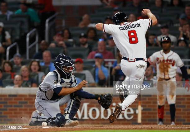 Francisco Mejia of the San Diego Padres drops the ball as Charlie Culberson of the Atlanta Braves scores on a RBI single hit by Ronald Acuna Jr #13...