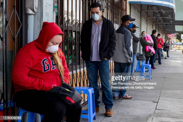 Francisco Montero of Richmond wears a mask while waiting with others in a long line outside of Terra Nova Clinic in the Fruitvale neighborhood of...
