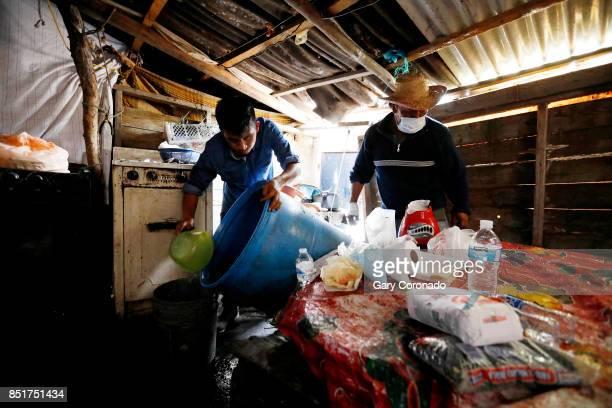 Francisco Ocadiz left along with his father Sergio Ocadiz empty a 50gallon drum into buckets so Franciso can go retrieve more water at their home in...