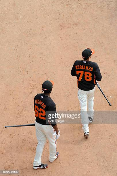 Francisco Peguero and Ehire Adrianza walk towards the batting cages before a spring training game against the Los Angeles Dodgers at Scottsdale...