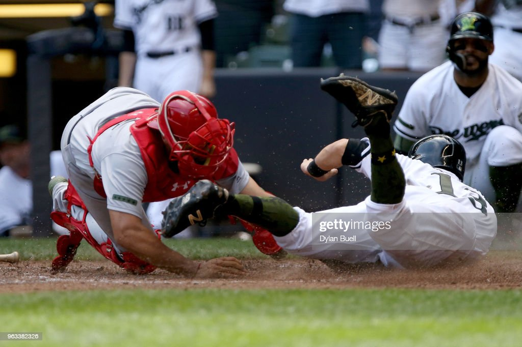 Francisco Pena #46 of the St. Louis Cardinals tags out Tyler Saladino #13 of the Milwaukee Brewers at home plate in the fourth inning at Miller Park on May 28, 2018 in Milwaukee, Wisconsin. MLB players across the league are wearing special uniforms to commemorate Memorial Day.