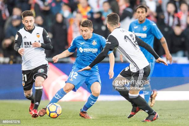 Francisco Portillo Soler of Getafe CF in action against Martin Montoya Torralbo of Valencia CF and Jose Luis Gaya Pena of Valencia CF during the La...