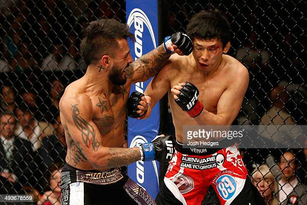 Francisco Rivera punches Takeya Mizugaki in their bantamweight bout during the UFC 173 event at the MGM Grand Garden Arena on May 24, 2014 in Las...