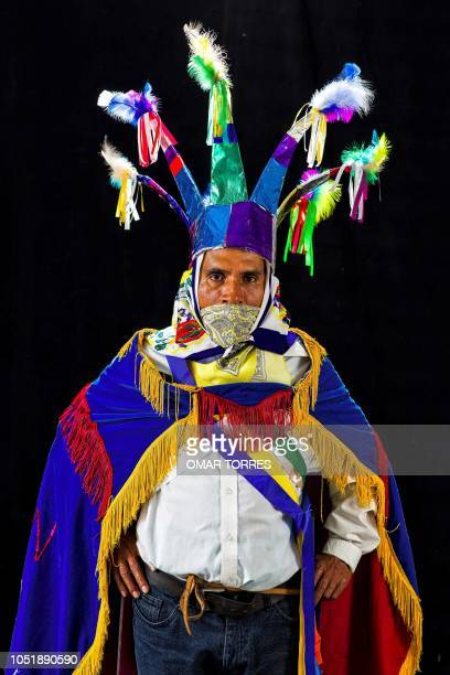 Francisco Sanchez Medel poses for a photograph with his traditional costume during the presentation of the Huey Atlixcayotl Festival on September 29...