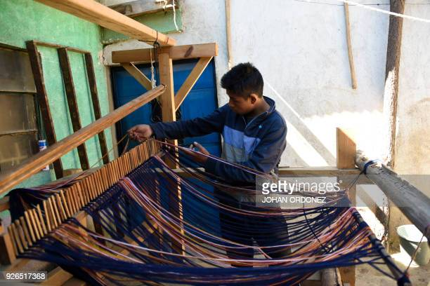 Francisco Tambriz prepares to weave fabric rolls inspired by Mayan costumes for the making of reusable bags in an attempt to put a curb on the abuse...