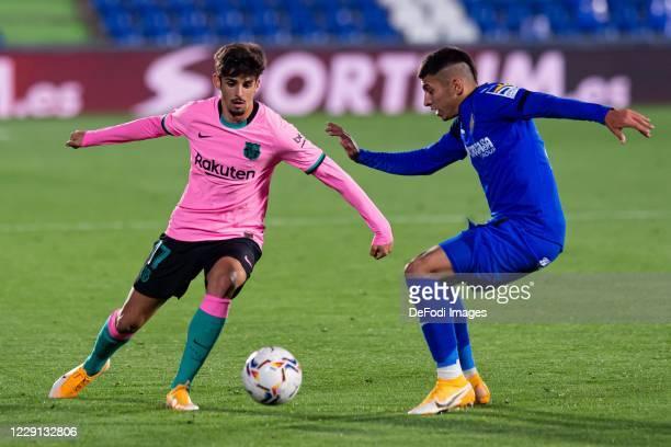 Francisco Trincao of FC Barcelona and Mathias Olivera of Getafe CF battle for the ball during the La Liga Santader match between Getafe CF and FC...