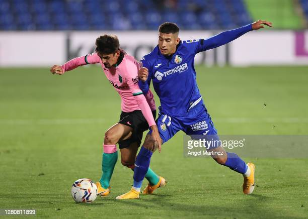 Francisco Trincao of FC Barcelona competes for the ball with Mathias Olivera of Getafe CF during the La Liga Santander match between Getafe CF and FC...