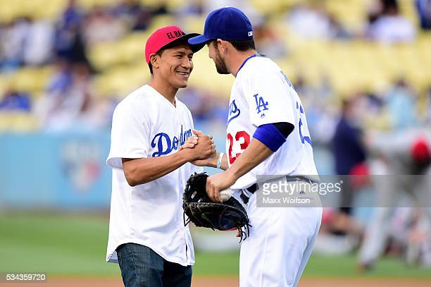 Francisco Vargas the WBC super featherweight champion shakes hands with Adrian Gonzalez of the Los Angeles Dodgers after throwing out the ceremonial...