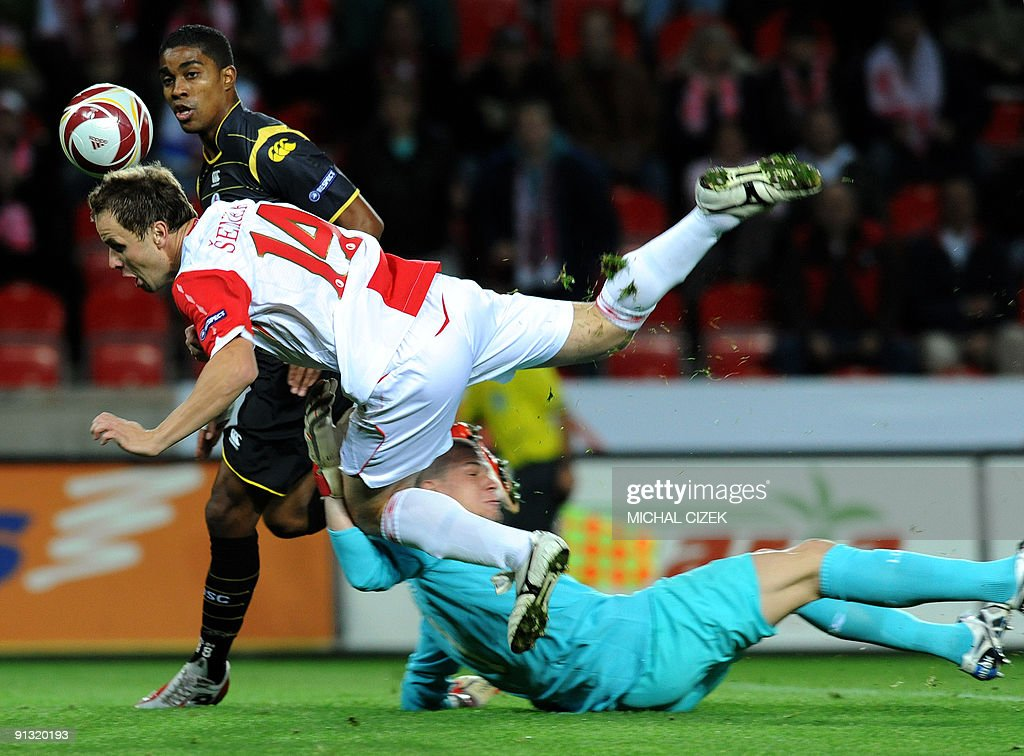 Franck Beria of Lille (L/background) looks at the ball as Zdenek Senkerik of Slavia Prague (white jersey) is tackled by Lille's goalkeeper Ludovic Btelle (R) during the UEFA Europa League Group B football match between Slavia Prague and Lille on October 1, 2009 in Prague.