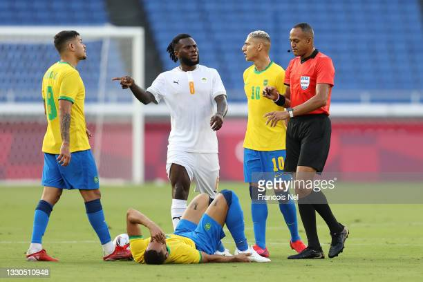 Franck Kessie of Team Ivory Coast interacts with Match Referee, Ismail Elfath during the Men's First Round Group D match between Brazil and Cote...