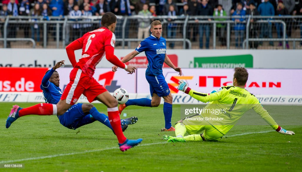 Franck Kom of Karlsruhe challenges Michael Rensing of Fortuna Duesseldorf during the Second Bundesliga match between Karlsruher SC and Fortuna Duesseldorf at Wildparkstadion on March 19, 2017 in Karlsruhe, Germany.