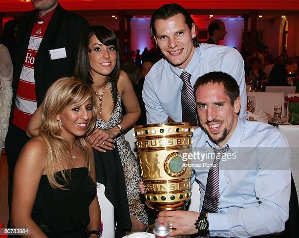 Franck Ribery and his wife Wahiba Ribery hold the trophy as Daniel van Buyten and his girlfriend Celine smile during the Bayern Munich champions...