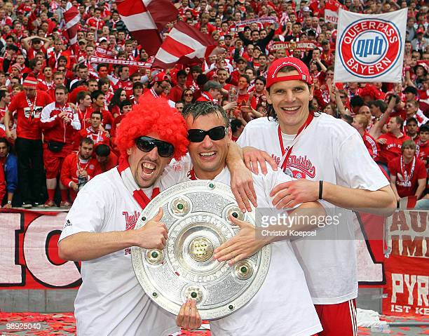 Franck Ribery Ivica Olic and Daniel van Buyten of Bayern present the German Championship trophy after winning 31 the Bundesliga match between Hertha...