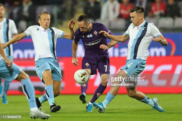 Franck Ribery of ACF Fiorentina battles for the ball with Lucas Leiva and Gil Patrick of SS Lazio during the Serie A match between ACF Fiorentina and...