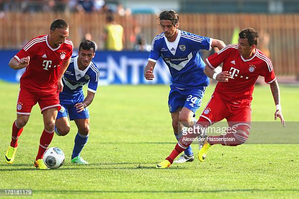 Franck Ribery of Bayern Muenchen and his team mate Mario Mandzukic battle for the ball with Ahmad Benali of Brescia and his team mate Massimo Paci...