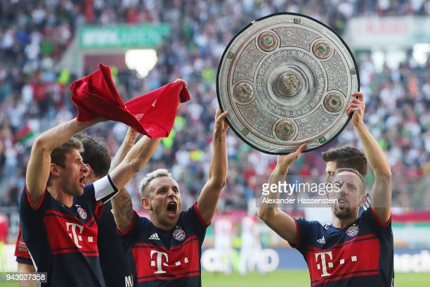 Franck Ribery of Bayern Muenchen and Rafinha of Bayern Muenchen celebrate with a replica of the champions trophy after Muenchen won the championship...