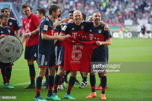 Franck Ribery of Bayern Muenchen Arjen Robben of Bayern Muenchen and Thomas Mueller of Bayern Muenchen display a shirt showing a 6 after they won the...