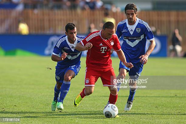 Franck Ribery of Bayern Muenchen battles for the ball with Ahmad Benali of Brescia and his team mate Massimo Paci during the friendly match between...