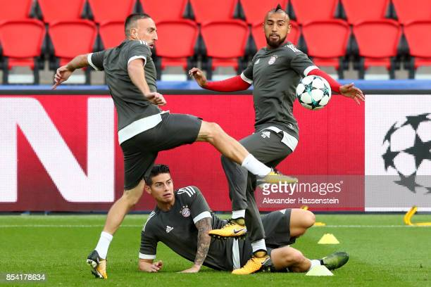 Franck Ribery of Bayern Muenchen battles for the ball with his team mates James Rodriquez and Arturo Vidal during a training session ahead of the...