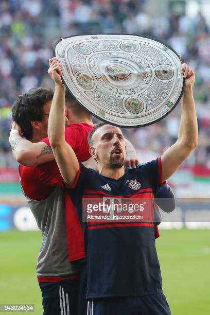 Franck Ribery of Bayern Muenchen celebrate with a replica of the champions trophy after Muenchen won the championship after the Bundesliga match...