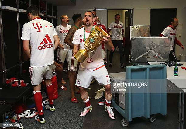 Franck Ribery of Bayern Muenchen celebrates victory with the trophy in the dressing room after the DFB Cup final match between FC Bayern Muenchen and...