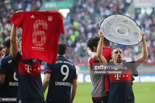 Franck Ribery of Bayern Muenchen celebrates with a replica of the champions trophy after Muenchen won the championship while Thomas Mueller of Bayern...