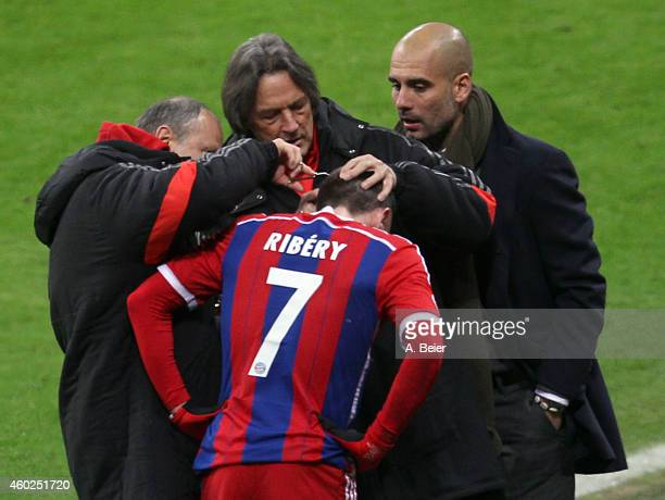 Franck Ribery of Bayern Muenchen is treated at a head injury by team doctor HansWilhelm MuellerWohlfahrt as team coach Josep Guardiola watches them...