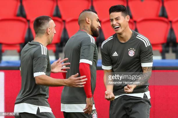 Franck Ribery of Bayern Muenchen jokes with his team mates James Rodriquez and Arturo Vidal during a training session ahead of the UEFA Champions...