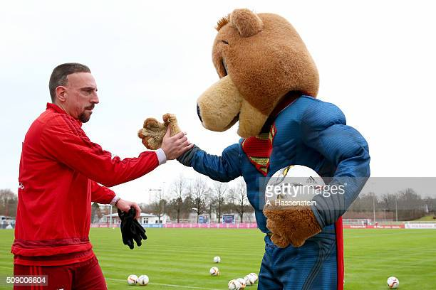 Franck Ribery of Bayern Muenchen reacts with mascot Bernie dressed as Superman prior to a training session at Bayern Muenchen's training ground...