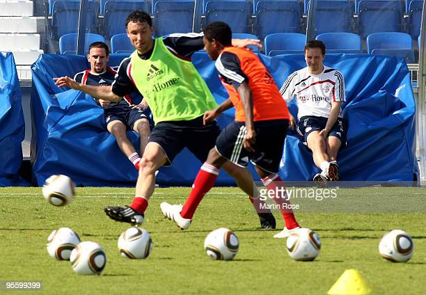 Franck Ribery of Bayern Muenchen watches Mark van Bommel und David Abala during the FC Bayern Muenchen training session at the Al Nasr training...