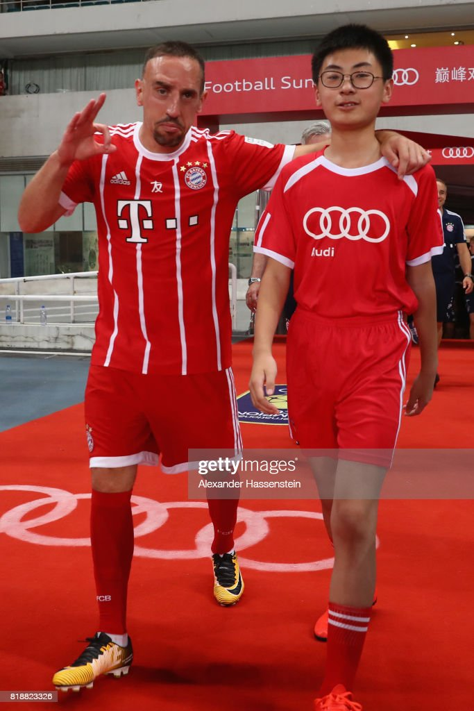 Franck Ribery of Bayern Muenchenjokes with the escort kid as he walk in for the Audi Football Summit 2017 match between Bayern Muenchen and Arsenal FC at Shanghai Stadium during the Audi Summer Tour 2017 on July 19, 2017 in Shanghai, China.