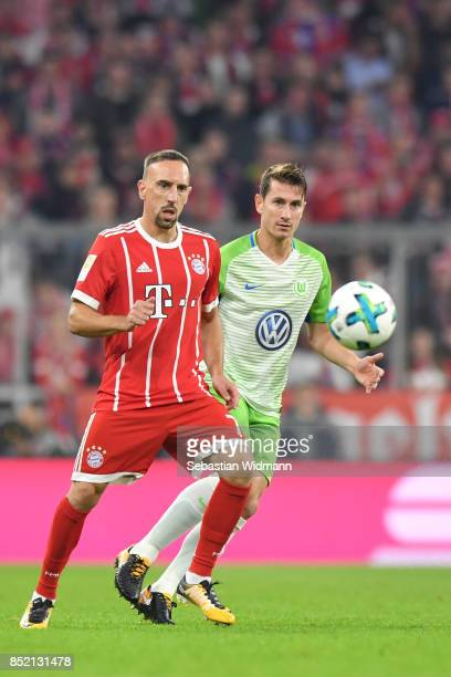 Franck Ribery of FC Bayern Muenchen and Paul Verhaegh of Wolfsburg compete for the ball during the Bundesliga match between FC Bayern Muenchen and...