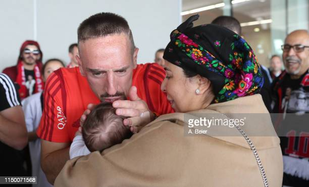 Franck Ribery of FC Bayern Muenchen kisses his baby as he is welcomed by wife Wahiba and family and friends during his arrival for the Bundesliga...