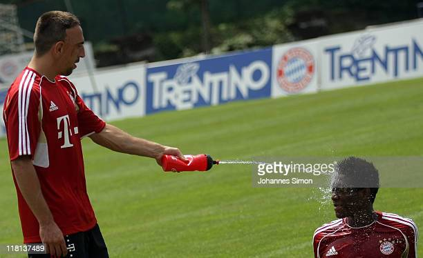 Franck Ribery of FC Bayern Muenchen refreshes team mate David Alaba with water during a training session on July 4 2011 in Riva del Garda Italy