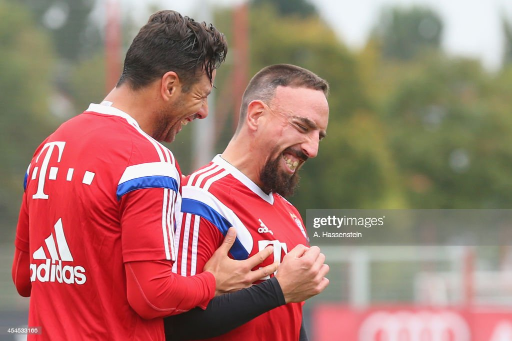 Franck Ribery of FC Bayern Muenchen smiles with his team mate Claudio Pizarro (L) during a training session at Bayern Muenchen's trainings ground Saebener Strasse on on September 3, 2014 in Munich, Germany.