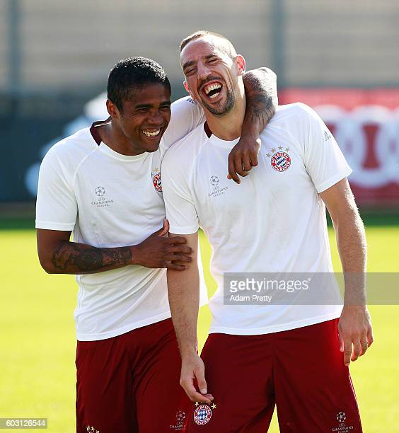 Franck Ribery of FC Bayern Munich shares a laugh with Douglas Costa at FC Bayern Munich training grounds before their Champions League match against...