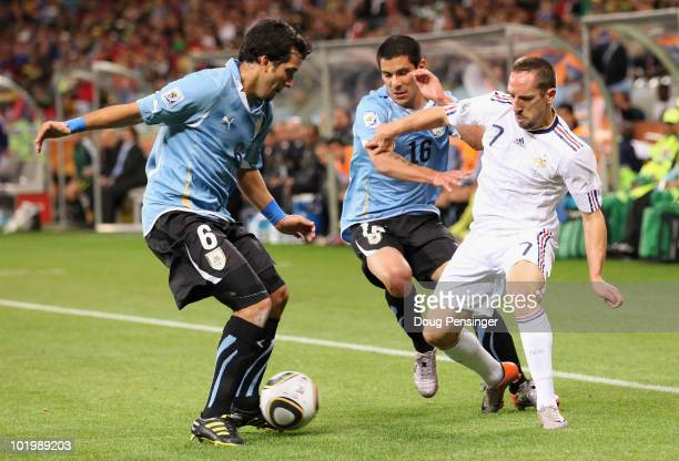 Franck Ribery of France is closed down by Mauricio Victorino and Maximiliano Pereira of Uruguay during the 2010 FIFA World Cup South Africa Group A...