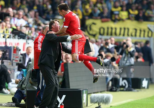 Franck Ribery of Muenchen celebrates with head coach Louis van Gaal after scoring his team's third goal the Bundesliga match between Borussia...