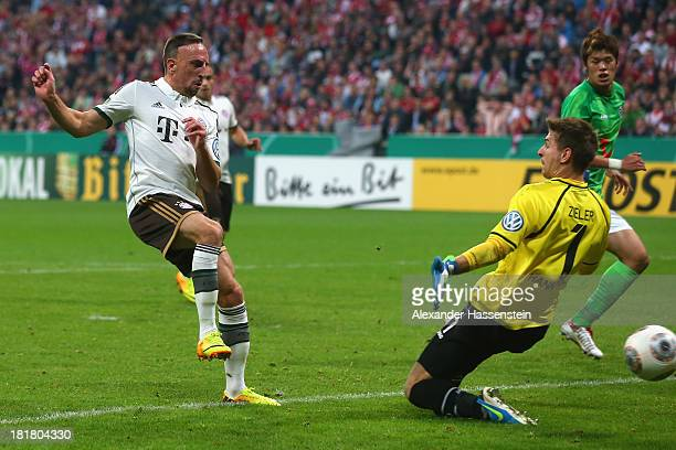 Franck Ribery of Muenchen scores the 4rd team goal against Hiroki Sakai of Hannover and his keeper Ron-Robert Zieler during the DFB Cup match between...