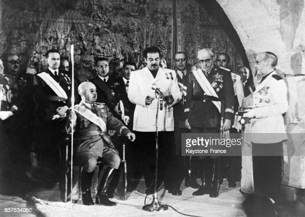 Franco assis à droite tenant en main une sorte de sceptre écoute le discours de félicitations du maire de Burgos Espagne en 1946